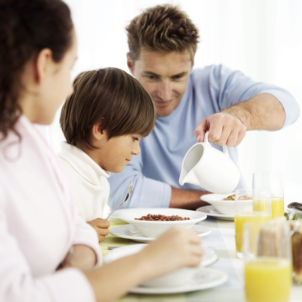 Young Father Pouring Milk into Bowl of Cereal for Young Boy (6-8)